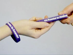 "Hands passing along a bracelet with the words ""A Promise to Amanda"""